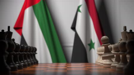 syrian : Flags of UAE and Syria behind pawns on the chessboard. Chess game or political rivalry related 3D animation
