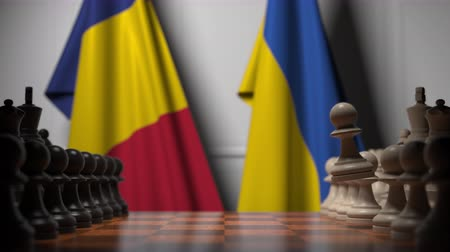 rumena : Flags of Romania and Ukraine behind pawns on the chessboard. Chess game or political rivalry related 3D animation