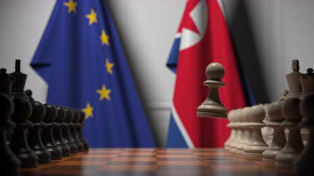 соперничество : Flags of EU and North Korea behind pawns on the chessboard. Conceptual 3D animation