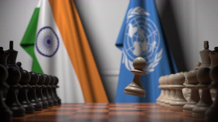 diplomatie : Flags of India and United Nations behind pawns on the chessboard. Conceptual editorial 3D animation