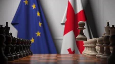 конкурировать : Flags of EU and Georgia behind pawns on the chessboard. Chess game or political rivalry related 3D animation Стоковые видеозаписи