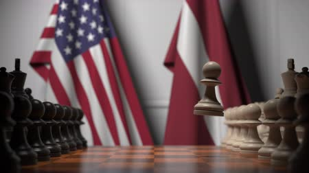 šachy : Flags of USA and Latvia behind pawns on the chessboard. Chess game or political rivalry related 3D animation