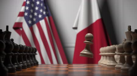 maltština : Flags of USA and Malta behind pawns on the chessboard. Chess game or political rivalry related 3D animation