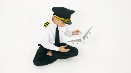 capitão : Boy in pilots uniform playing with toy airliner