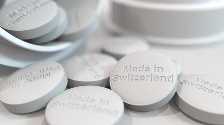 koşullar : Pills with MADE IN SWITZERLAND text on them. National pharmaceutical industry related 3D animation Stok Video