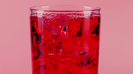 sede : Red soft drink with ice cubes in a glass against pink background, close-up slow motion shot on Red