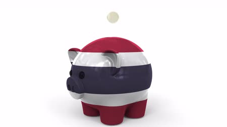 centavo : Coins fall into piggy bank painted with flag of Thailand. National banking system or savings related conceptual 3D animation Stock Footage