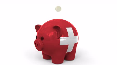 centavo : Coins fall into piggy bank painted with flag of Switzerland. National banking system or savings related conceptual 3D animation Stock Footage