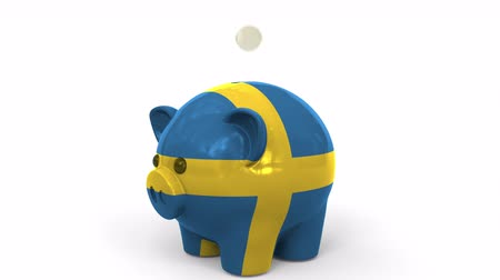 penny : Coins fall into piggy bank painted with flag of Sweden. National banking system or savings related conceptual 3D animation