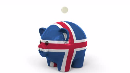 налоги : Coins fall into piggy bank painted with flag of Iceland. National banking system or savings related conceptual 3D animation Стоковые видеозаписи