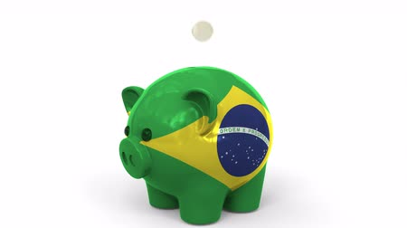 centavo : Coins fall into piggy bank painted with flag of Brazil. National banking system or savings related conceptual 3D animation Stock Footage