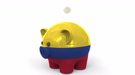 colômbia : Coins fall into piggy bank painted with flag of Colombia. National banking system or savings related conceptual 3D animation