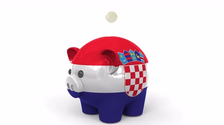 penny : Coins fall into piggy bank painted with flag of Croatia. National banking system or savings related conceptual 3D animation