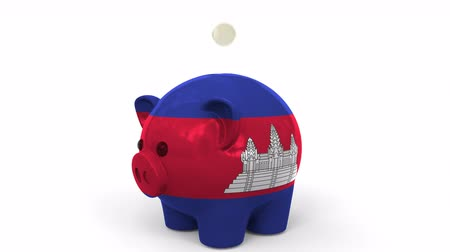 kamboçyalı : Coins fall into piggy bank painted with flag of Cambodia. National banking system or savings related conceptual 3D animation