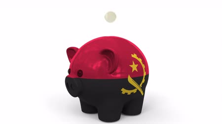 centavo : Coins fall into piggy bank painted with flag of Angola. National banking system or savings related conceptual 3D animation