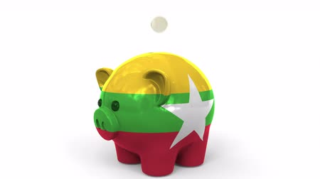 fondo industrial : Coins fall into piggy bank painted with flag of Myanmar. National banking system or savings related conceptual 3D animation Archivo de Video