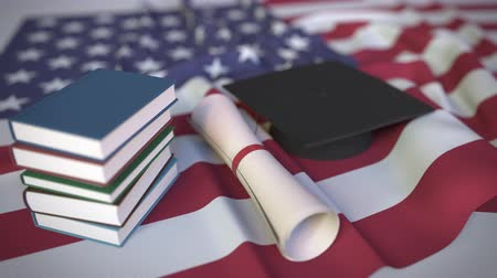 mortarboard : Graduation cap, books and diploma on the American flag. Higher education in the USA related conceptual 3D animation Stock Footage