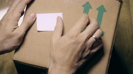 armenia : Warehouse worker places sticker with flag of Armenia on the box. Armenian import or export related clip