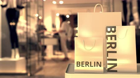 retailer : Shopping bags with BERLIN text against blurred store. German shopping related clip Stock Footage