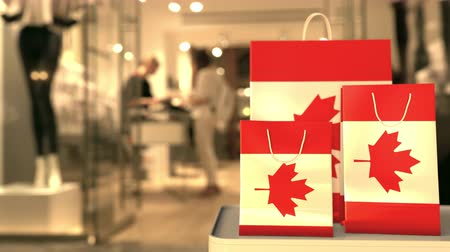 canadense : Shopping bags with flag of Canada against blurred store. Canadian shopping related clip Stock Footage