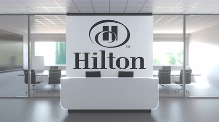 oficial : Logo of HILTON on a wall in the modern office, editorial conceptual 3D animation
