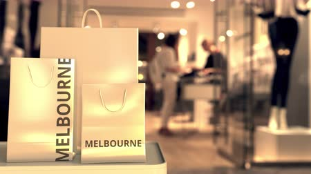 italiaanse vlag : Paper shopping bags with MELBOURNE text against blurred store. Italian shopping related clip