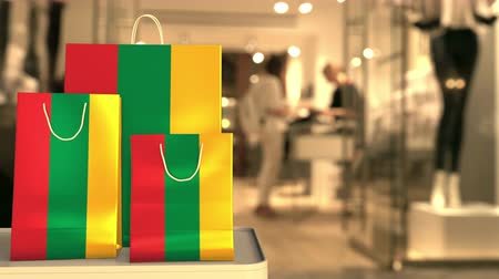 flag of lithuania : Flag of Lithuania on the paper shopping bags against blurred store entrance. Retail related clip Stock Footage