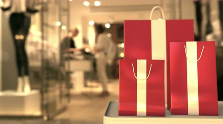 retailer : Flag of Latvia on the paper shopping bags against blurred store entrance. Retail related clip Stock Footage