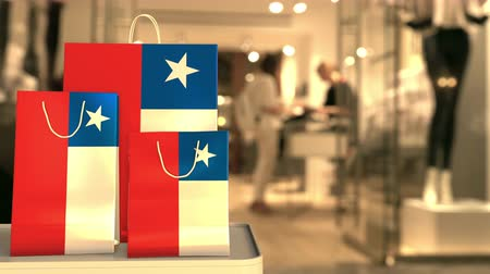 скидка : Flag of Chile on the paper shopping bags against blurred store entrance. Retail related clip