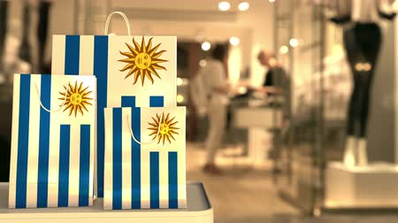 Уругвай : Flag of Uruguay on the paper shopping bags against blurred store entrance. Retail related clip