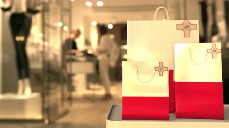 maltština : Flag of Malta on the paper shopping bags against blurred store entrance. Retail related clip