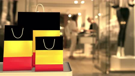 commessa : Flag of Belgium on the paper shopping bags against blurred store entrance. Retail related clip