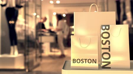 скидка : Shopping bags with BOSTON text against blurred store. American shopping related clip Стоковые видеозаписи