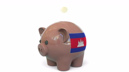 centavo : Putting money into piggy bank with flag of Cambodia. Tax system system or savings related conceptual 3D animation