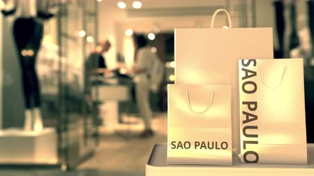 sao : Shopping bags with SAO PAULO text against blurred store. Brazilian shopping related clip Stock Footage