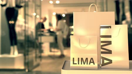 lima : Shopping bags with LIMA text against blurred store. Peruvian retail related clip Stock Footage