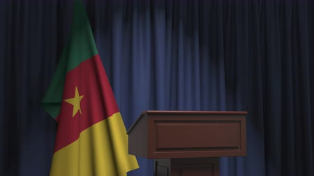 press conference : Flag of Cameroon and speaker podium tribune. Political event or statement related conceptual 3D animation Stock Footage