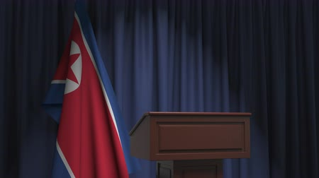 dprk : National flag of North Korea and speaker podium tribune. Political event or statement related conceptual 3D animation Stock Footage