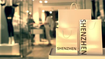 Шэньчжэнь : Shopping bags with SHENZHEN text against blurred store. Chinese retail related clip