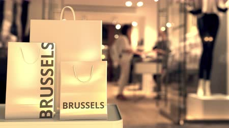 キャプション : Shopping bags with Brussels caption against blurred store entrance. Shopping in Belgium related 3D animation