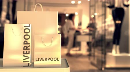 キャプション : Paper shopping bags with Liverpool caption against blurred store entrance. Retail in the United Kingdom related conceptual 3D animation