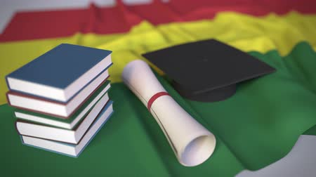mais alto : Graduation cap, books and diploma on the Bolivian flag. Higher education in Bolivia related conceptual 3D animation