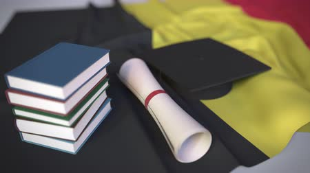 mortarboard : Graduation cap, books and diploma on the Belgian flag. Higher education in Belgium related conceptual 3D animation