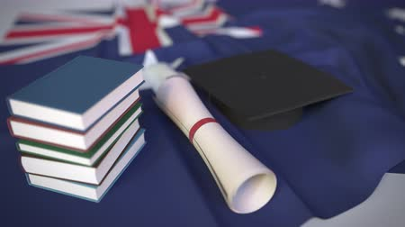 mortarboard : Graduation cap, books and diploma on the Australian flag. Higher education in Australia related conceptual 3D animation