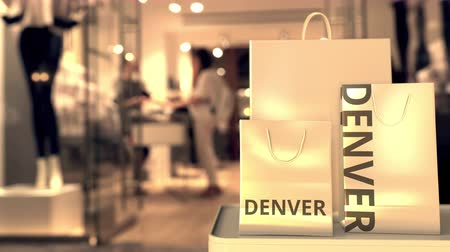 denver : Paper shopping bags with Denver caption against blurred store entrance. Retail in the United States related conceptual 3D animation