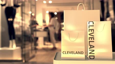 vetrina : Shopping bags with Cleveland caption against blurred store entrance. Shopping in the United States related conceptual 3D animation
