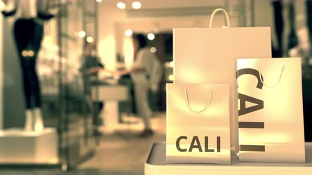 colômbia : Shopping bags with Cali caption against blurred store entrance. Shopping in Colombia related 3D animation