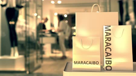 キャプション : Shopping bags with Maracaibo caption against blurred store entrance. Shopping in Venezuela related 3D animation