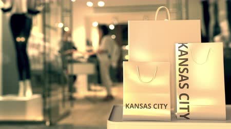 キャプション : Paper shopping bags with Kansas city caption against blurred store entrance. Retail in the United States related 3D animation