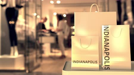 vetrina : Paper shopping bags with Indianapolis caption against blurred store entrance. Retail in the United States related conceptual 3D animation